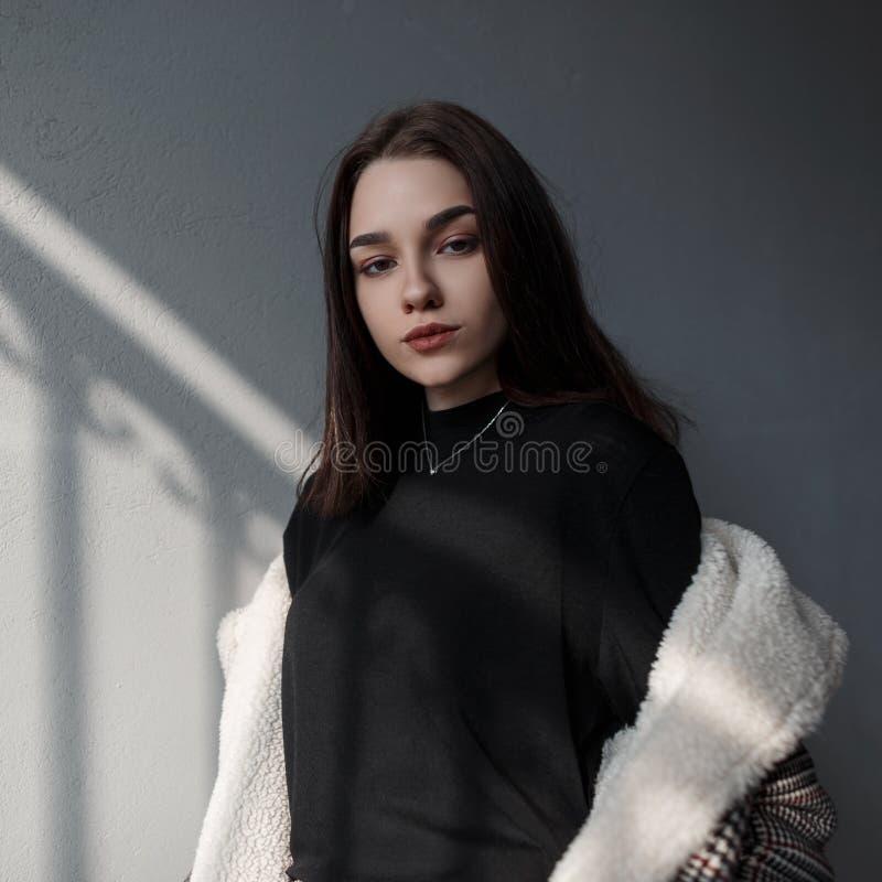 一件黑时髦衬衣的俏丽的年轻深色的妇女在有白色毛皮的一件时兴的格子花呢披肩夹克享用明亮的太阳 库存图片