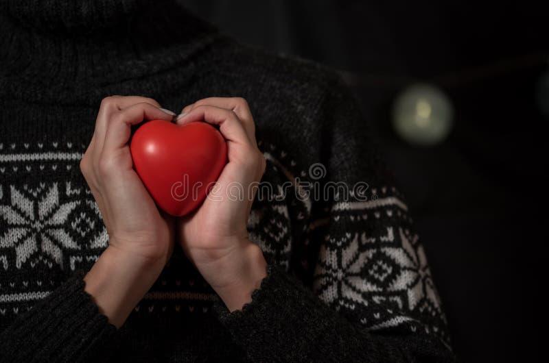 一件黑暗的冬天毛线衣的女孩在手中拿着大红心 免版税库存照片