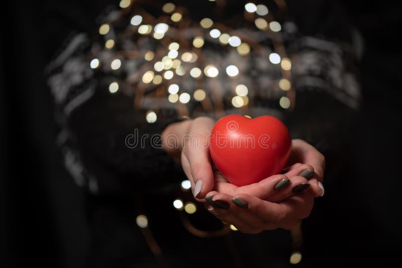 一件黑暗的冬天毛线衣的女孩在手中拿着大红心 库存图片