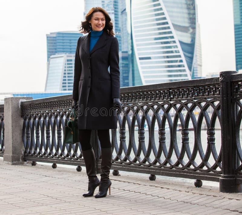 一件黑暗的外套的微笑的美丽的女商人 免版税库存图片