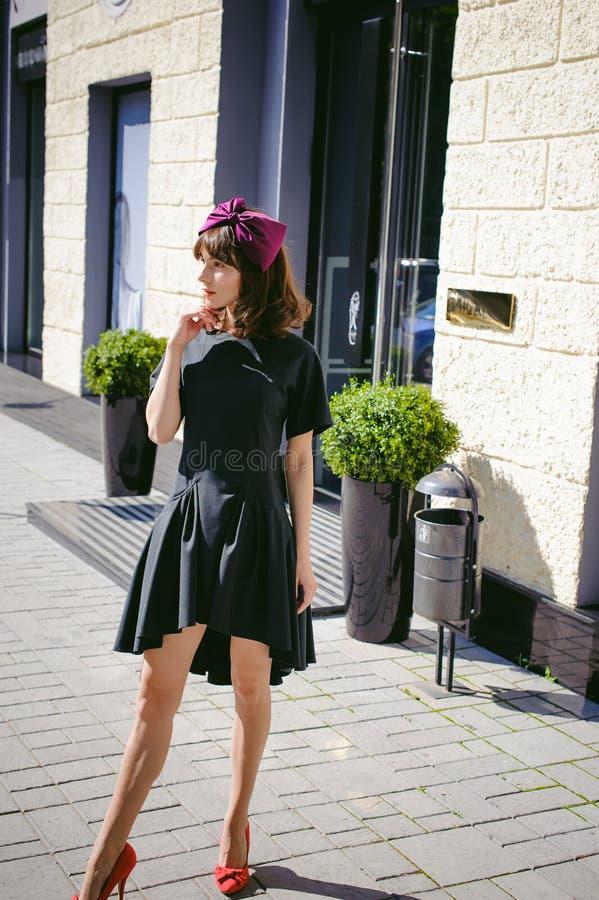 一件黑暗的时髦的礼服的美丽的妇女沿街道,近的精品店漫步 库存照片