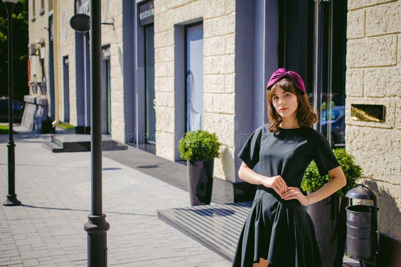 一件黑暗的时髦的礼服的美丽的妇女沿街道,近的精品店漫步 免版税库存图片