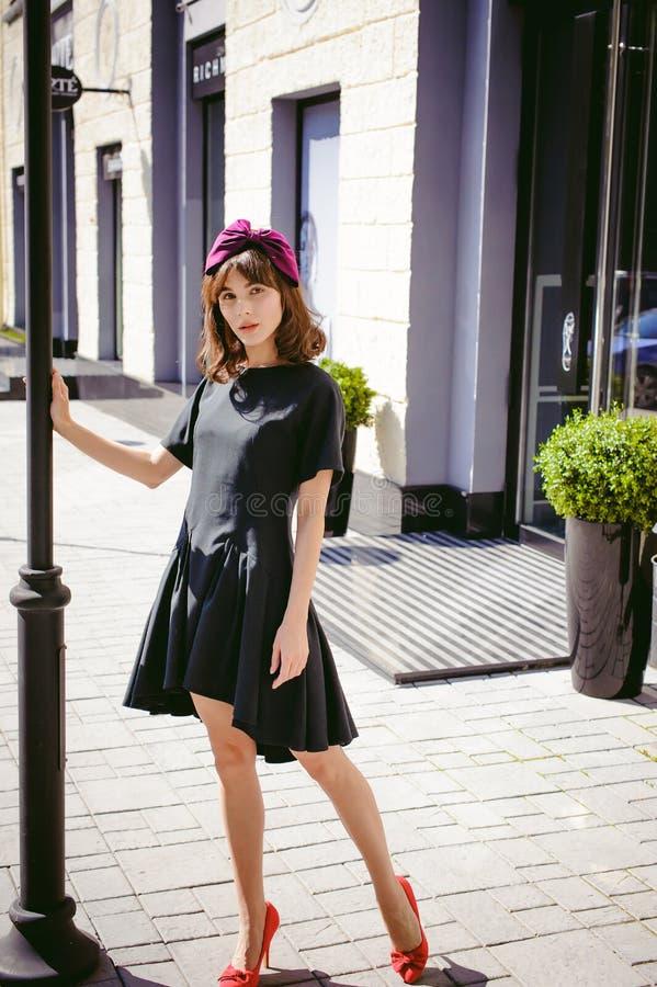 一件黑暗的时髦的礼服的美丽的妇女 一个时兴的女孩的纵向 库存照片