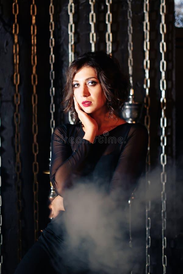一件黑礼服的一个美丽的深色的女孩抽水烟筒并且放掉抽烟 免版税库存图片