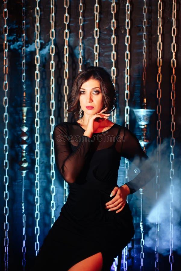 一件黑礼服的一个美丽的深色的女孩抽水烟筒并且放掉抽烟 库存图片