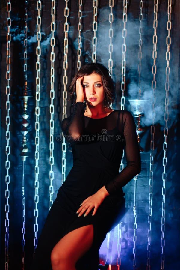 一件黑礼服的一个美丽的深色的女孩抽水烟筒并且放掉抽烟 免版税库存照片
