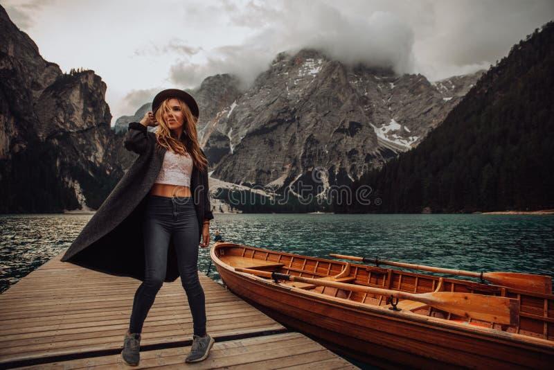 一件黑礼服的女孩在绿松石湖的背景山的 白云岩阿尔卑斯,lago di Braies 免版税图库摄影