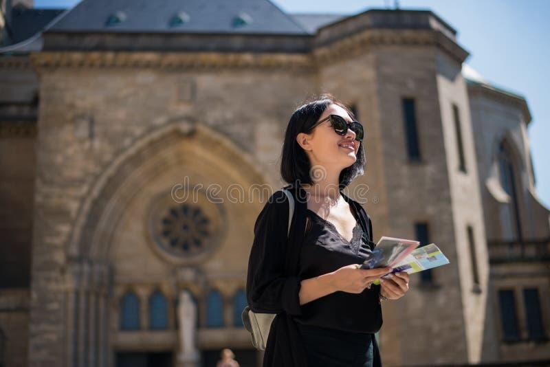 一件黑礼服的时髦的妇女走在老市的街道的附近卢森堡 漫步旅游的女孩 免版税图库摄影