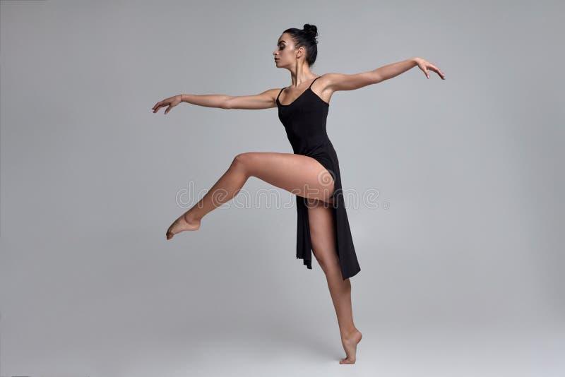 一件黑礼服的跳舞的芭蕾舞女演员 在灰色背景的当代优美的表现 库存照片