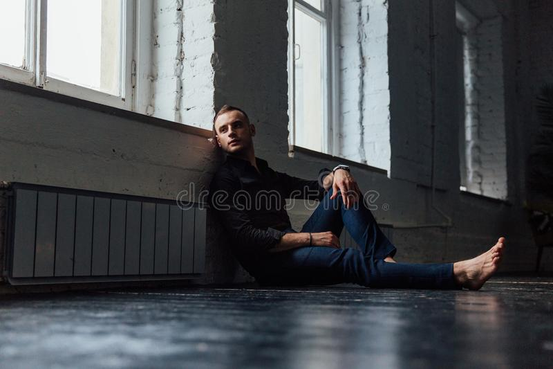 一件黑衬衣的画象英俊的时兴的人坐一个木地板由窗口 免版税库存照片