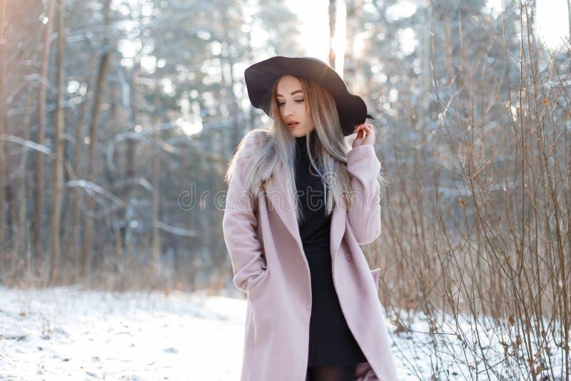 一件黑被编织的礼服的俏丽的美丽的年轻女人在摆在一件时髦的桃红色的外套的典雅的黑帽会议户外 免版税库存照片