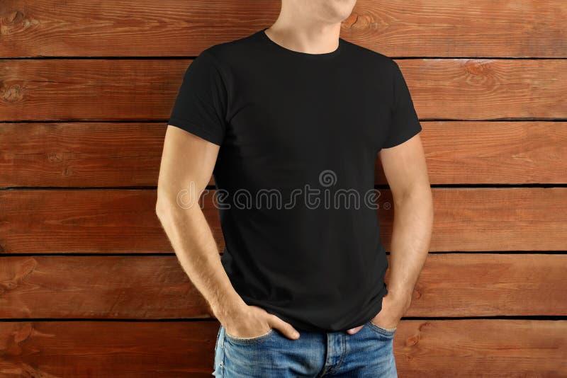一件黑T恤杉和蓝色牛仔裤的体育强壮的人在棕色木演播室背景 免版税库存图片