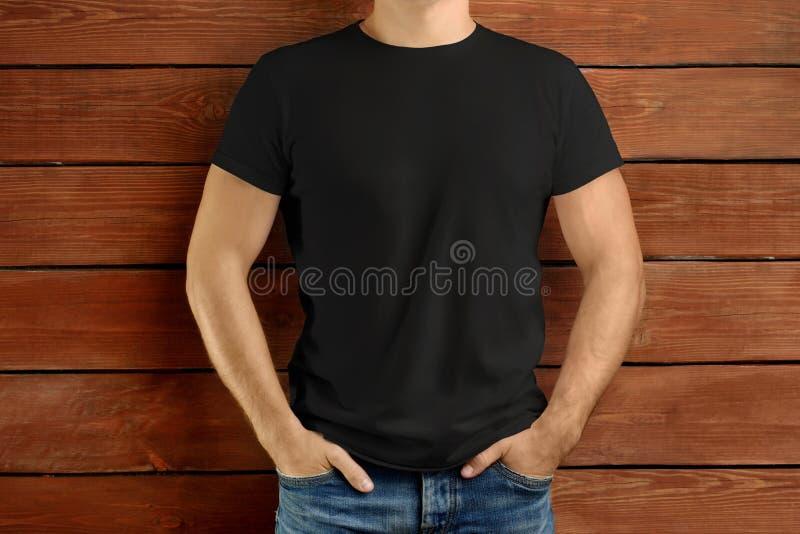 一件黑T恤杉和蓝色牛仔裤的强壮的亭亭玉立的人在棕色木演播室背景 免版税库存照片