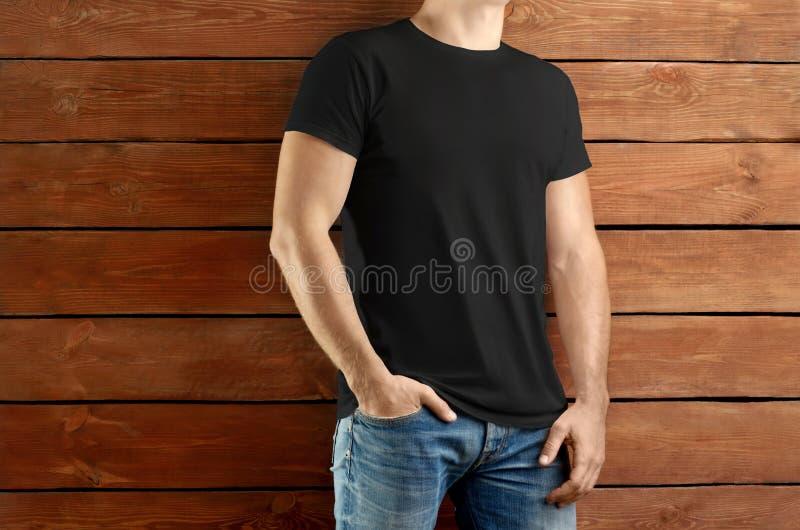 一件黑T恤杉和蓝色牛仔裤的强壮的亭亭玉立的人在棕色木演播室背景 库存图片