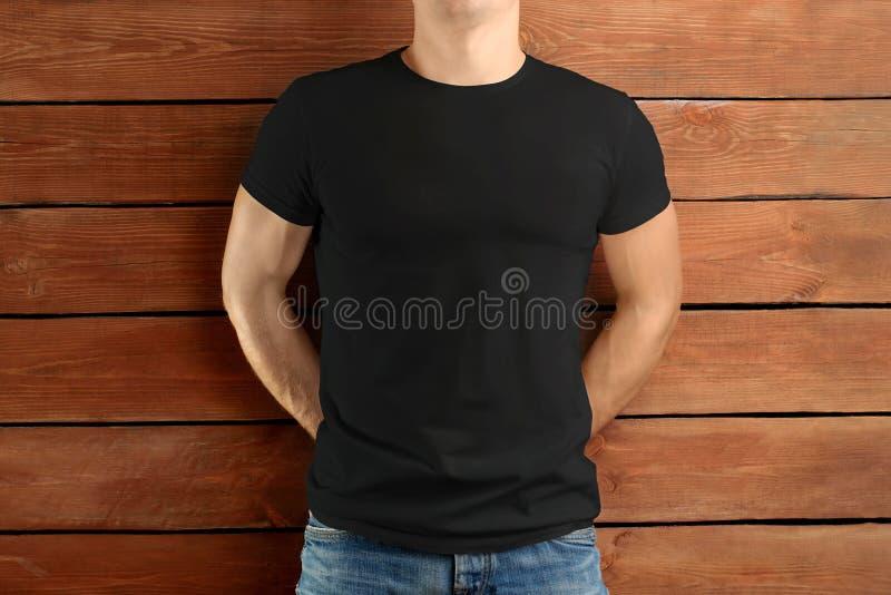 一件黑T恤杉和蓝色牛仔裤的肌肉适合的人在棕色木演播室背景 免版税图库摄影