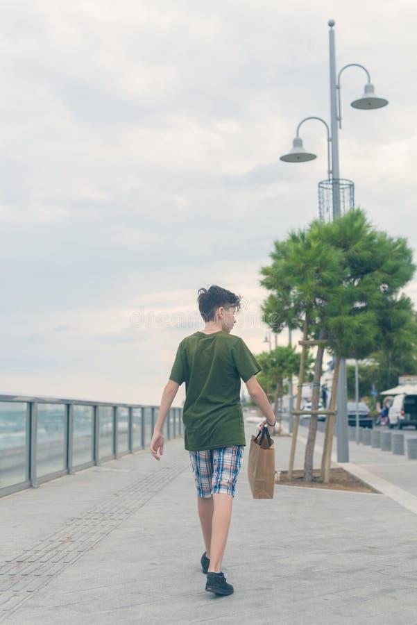 一件T恤杉和短裤步行的一个男孩在Finikoudes海滩-拉纳卡,塞浦路斯 库存照片