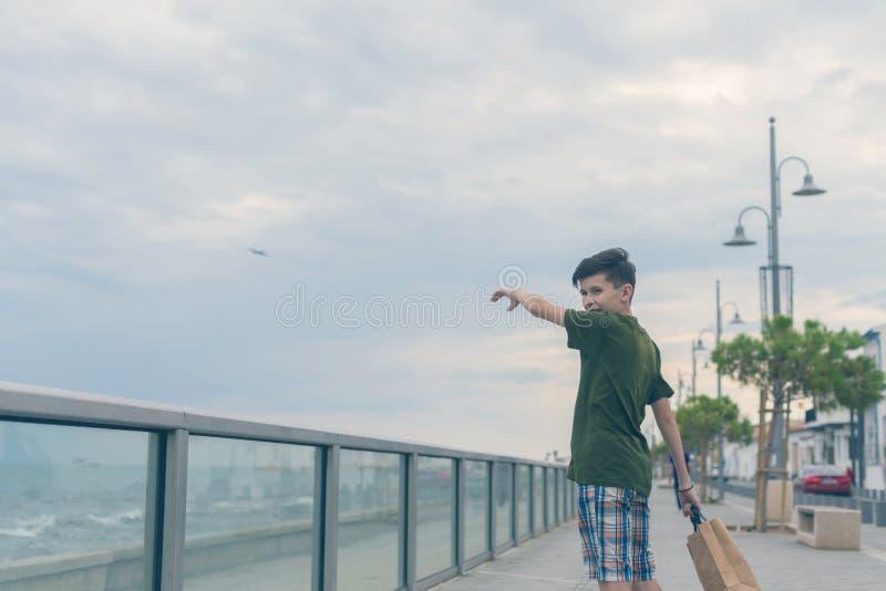 一件T恤杉和短裤步行的一个男孩在Finikoudes海滩-拉纳卡,塞浦路斯 免版税库存照片