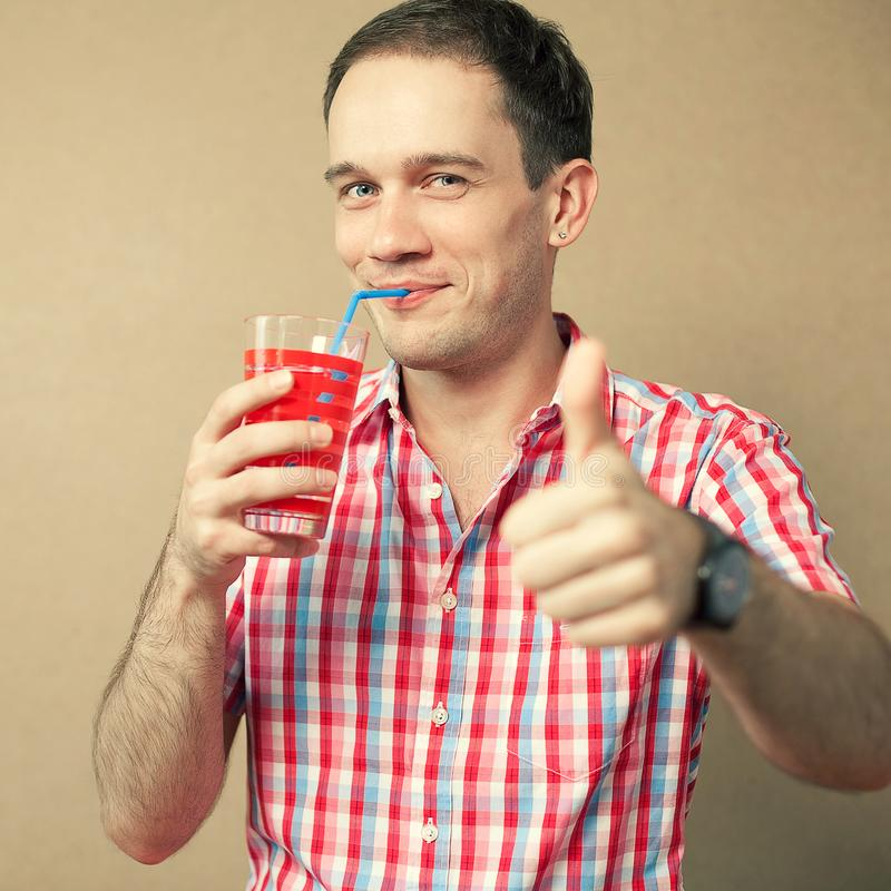 一份微笑的英俊的蓝眼睛的行家男孩饮料的滑稽的画象 库存照片