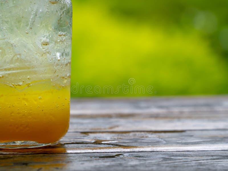 一份新桔子汽水饮料用在葡萄酒样式玻璃容器的冰充分填装了在玻璃的冰 安置在木书桌  库存图片