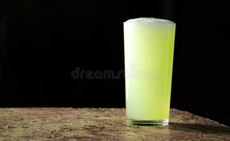 一份碳酸化合的苏打饮料的充分的杯,黄色在黑背景的颜色 免版税库存照片
