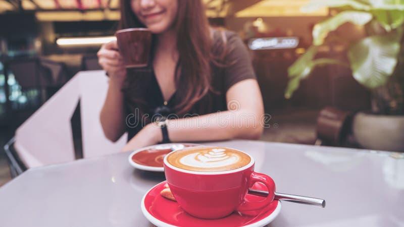 一份美丽的亚洲妇女举行的和饮用的咖啡的特写镜头图象与拿铁咖啡杯的在玻璃桌上 库存照片