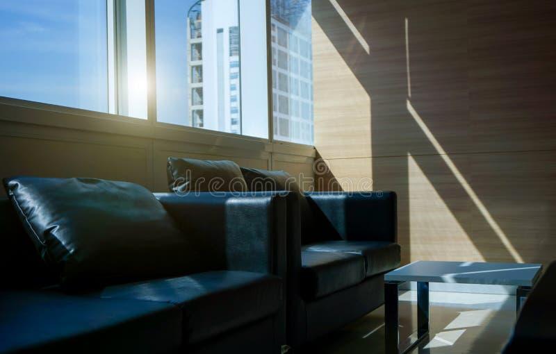 一休息室的黑沙发内部办公室和大厦视图的外面 免版税库存图片