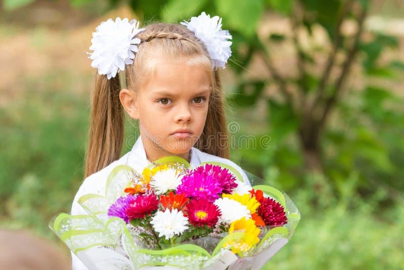 一位七年女小学生的画象有大花束的在手上 库存图片