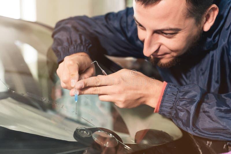 一位专业挡风玻璃安装工的特写镜头用一个特别聚合物填装在玻璃的一个裂缝通过注射器 免版税库存图片