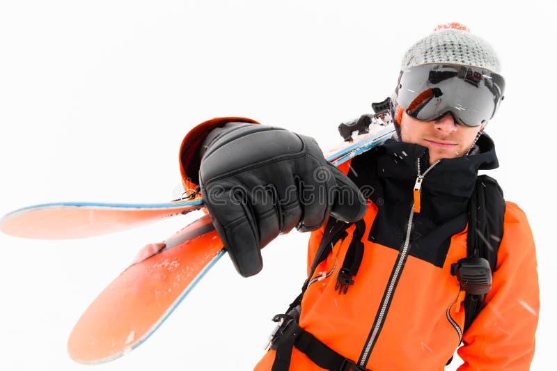 一位专业滑雪者运动员和与黑滑雪帽的橙色黑衣服的画象一个被编织的帽子的与在他的滑雪 免版税库存照片