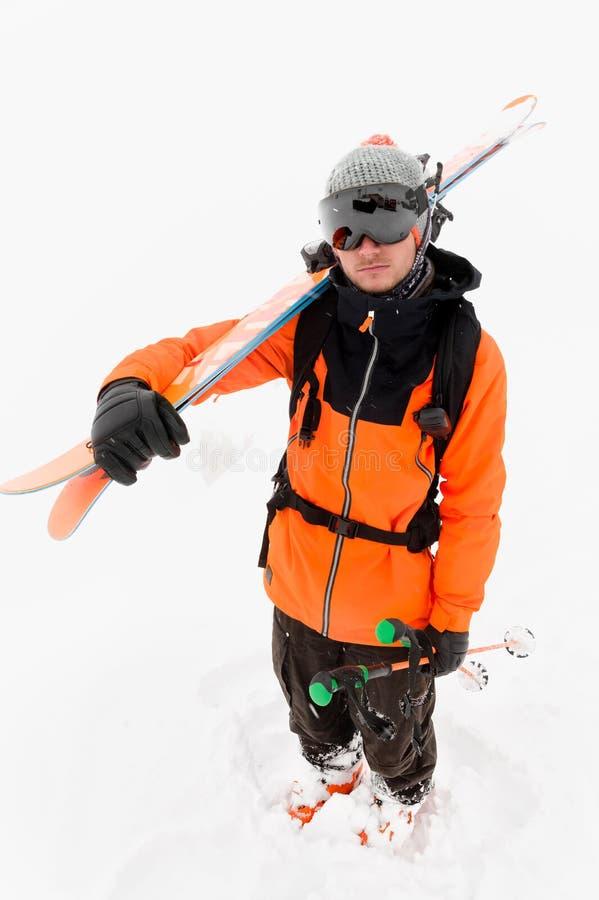 一位专业滑雪者运动员和与黑滑雪帽的橙色黑衣服的画象一个被编织的帽子的与在他的滑雪 免版税图库摄影