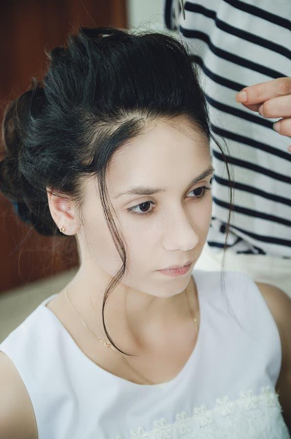 一位专业美发师做女孩的一种欢乐发型 特写镜头 库存图片