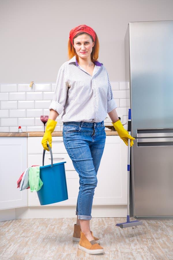 一位主妇的图象拿着一个平的湿拖把和桶有旧布的防护手套的,当清洗她的房子时 库存图片