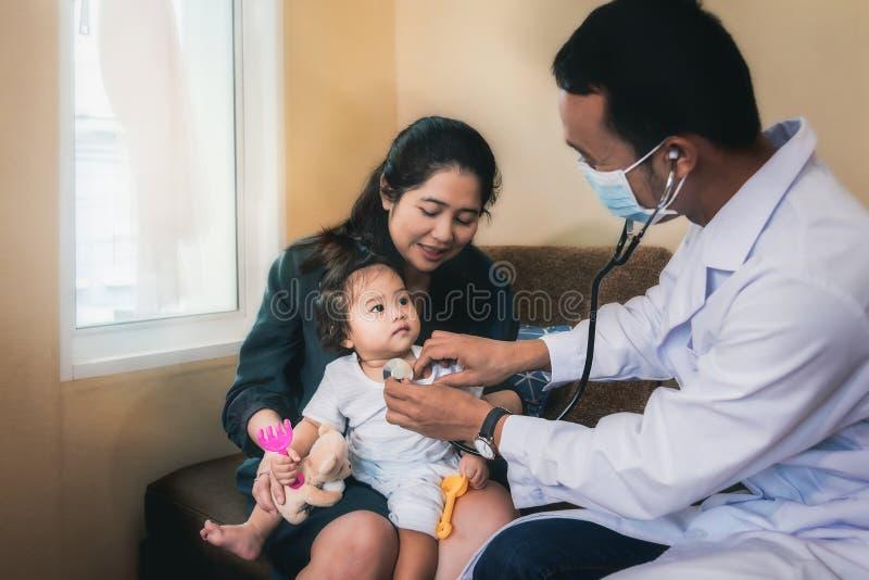 一位亚裔医生检查一病的女孩和havi的症状 免版税库存图片