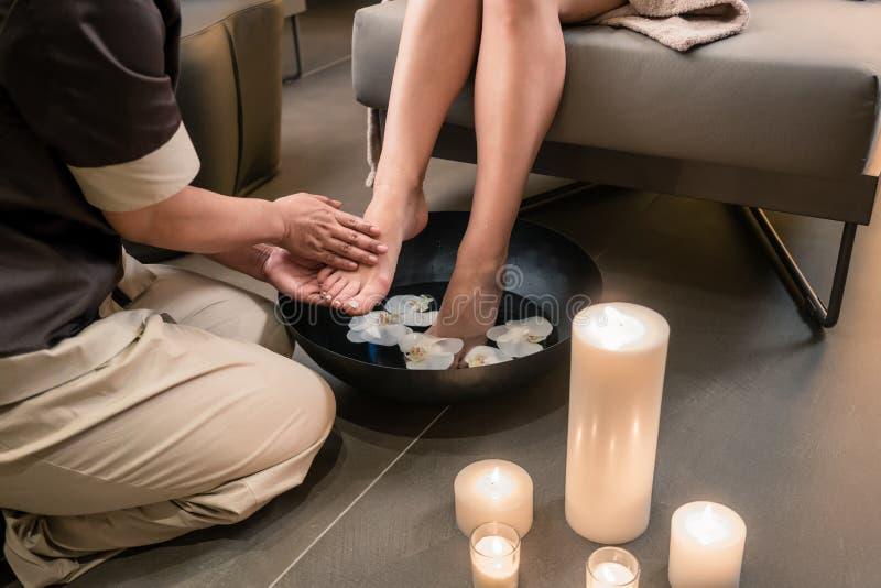 一位亚裔治疗师的手在脚洗涤的治疗期间的 免版税图库摄影