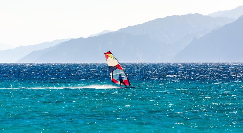 一位冲浪者在红海乘坐反对岩石海岸的背景在埃及 库存照片
