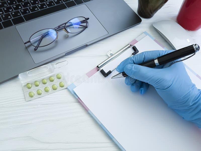 一位医生的手手套的在桌面,膝上型计算机写 库存图片