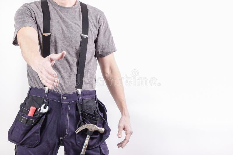 一位友好的杂物工/工匠伸出他的握手的手 免版税库存照片