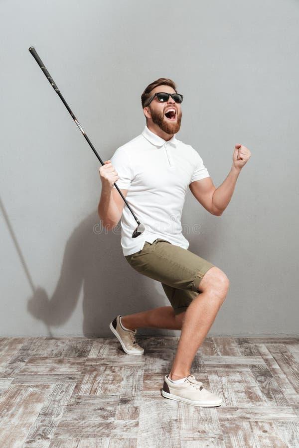 一位叫喊的高尔夫球运动员的全长图象太阳镜的 库存图片