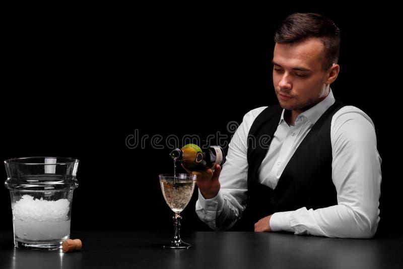 一位可爱的侍酒者倒在玻璃,有冰的一个桶,在黑背景的黄柏的香槟 库存照片