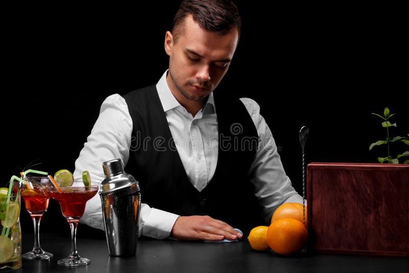 一位可爱的侍酒者抹一个酒吧柜台,桔子,柠檬,玛格丽塔酒玻璃,在黑背景的一台振动器 免版税库存照片