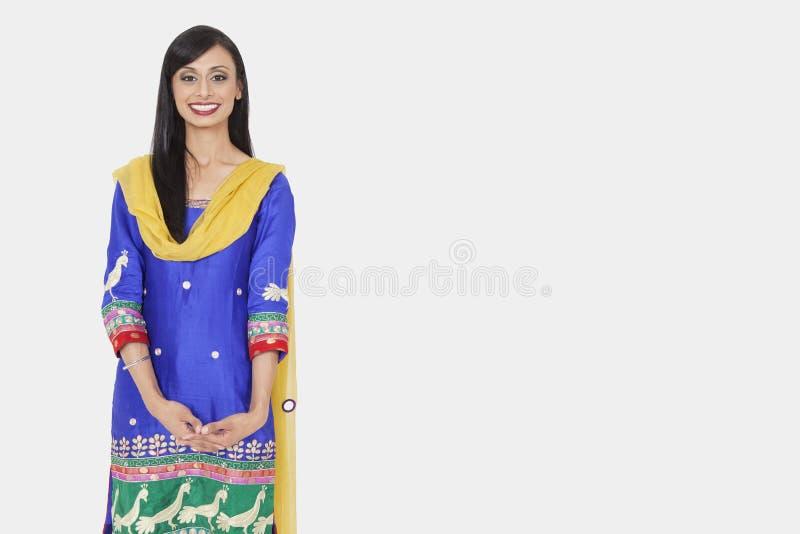 一位可爱的印地安女性的画象站立在灰色背景的传统穿戴的 库存图片