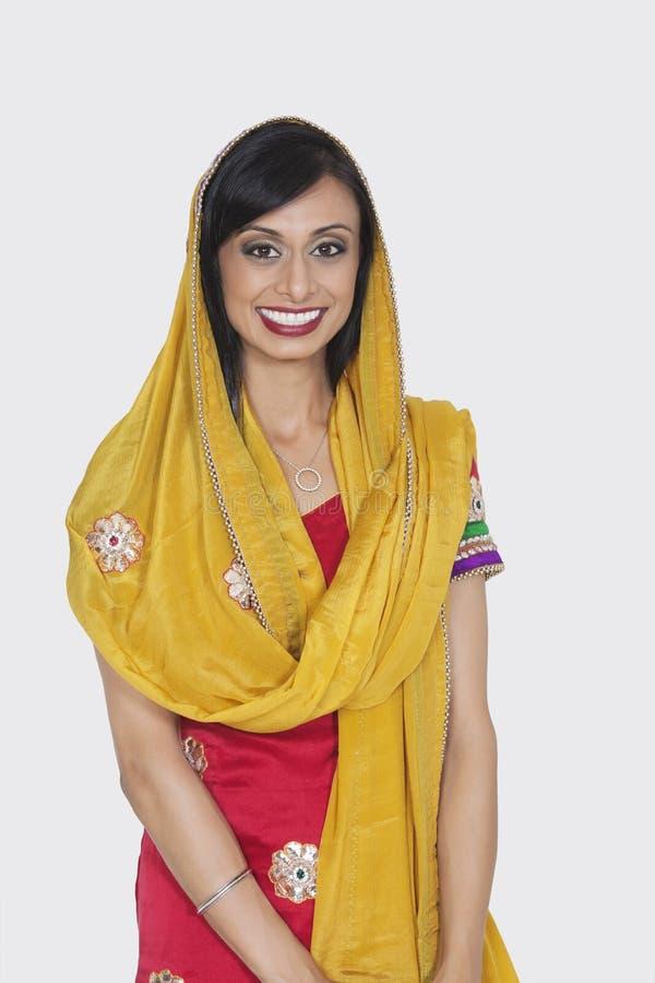 一位可爱的印地安女性的画象站立在灰色背景的传统穿戴的 免版税库存照片