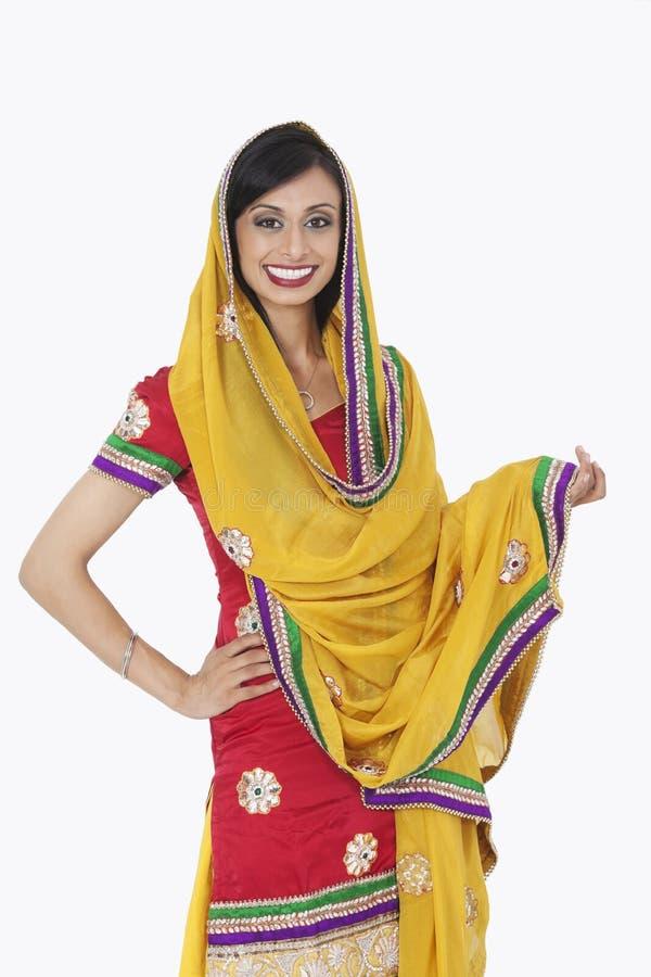 一位可爱的印地安女性的画象站立在白色背景的传统穿戴的 库存照片