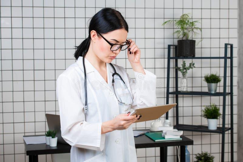 一位可爱的年轻女性医生或护士戴着眼镜的画象在白色制服有听诊器藏品片剂的 库存照片