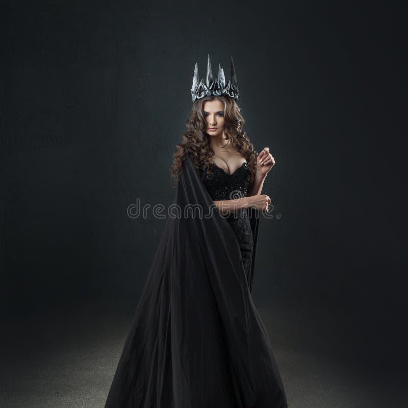 一位哥特式公主的画象 金属冠和黑斗篷的美丽的年轻深色的妇女 免版税库存图片