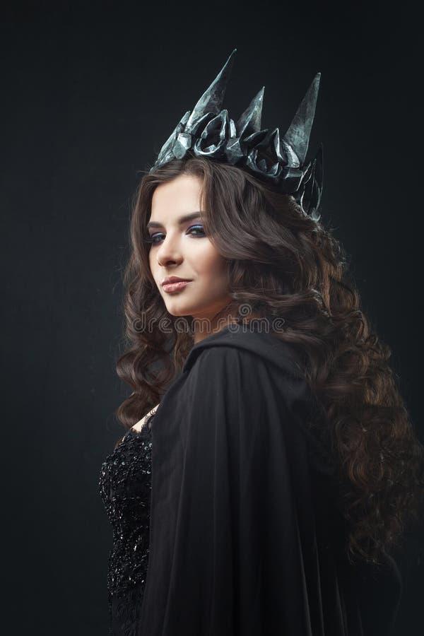 一位哥特式公主的画象 金属冠和黑斗篷的美丽的年轻深色的妇女 库存照片
