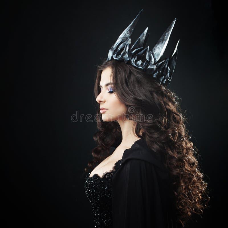 一位哥特式公主的画象 金属冠和黑斗篷的美丽的年轻深色的妇女 免版税库存照片