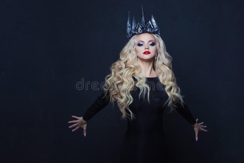 一位哥特式公主的画象 金属冠和黑斗篷的美丽的年轻白肤金发的妇女 免版税库存照片