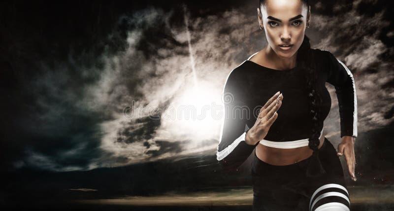 一位坚强的运动,女性短跑选手,跑在佩带在运动服、健身和体育刺激概念的日出 库存照片