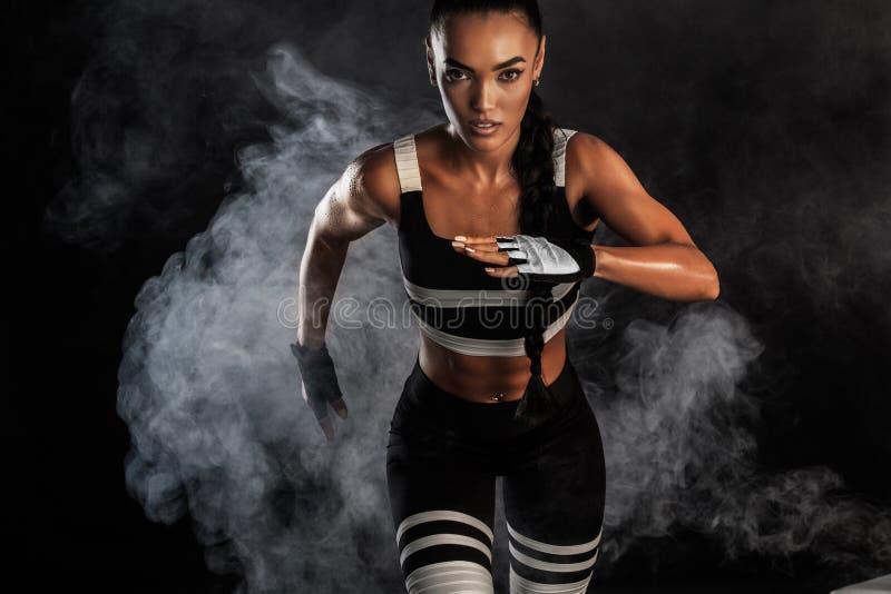 一位坚强的运动,女性短跑选手,跑在佩带在运动服、健身和体育刺激概念的日出 库存图片